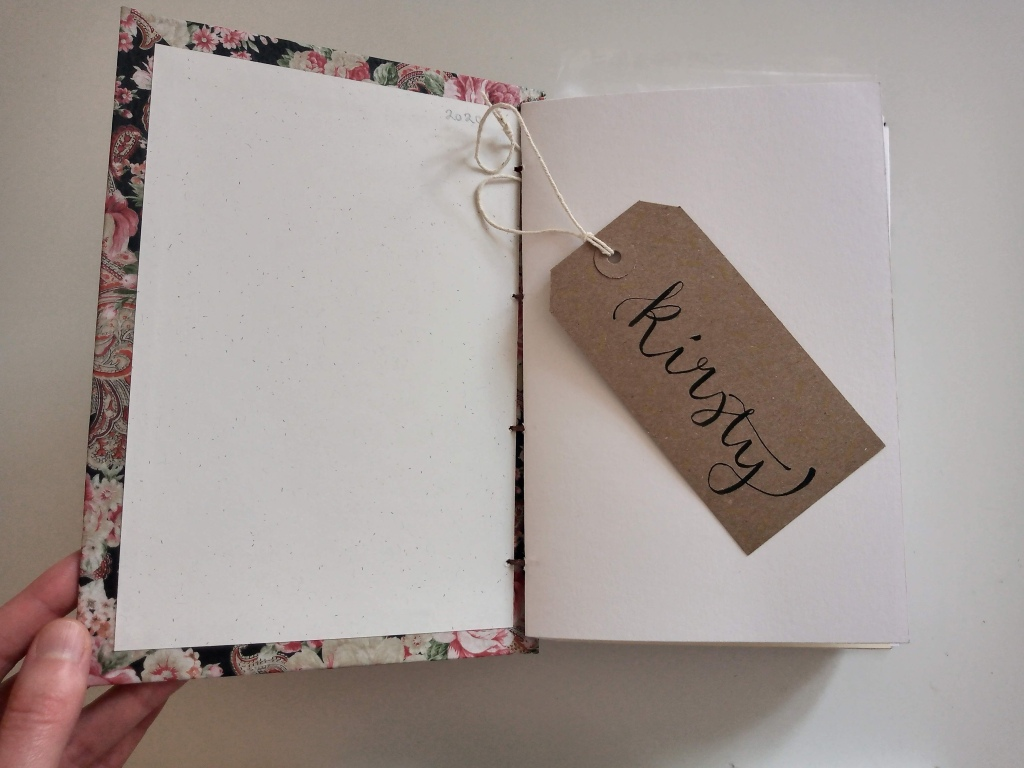 sketchbook handmade with coptic bookbinding method. Brush lettered gift tag with name on.